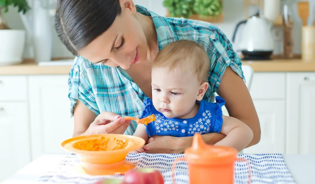 A young mother feeding her baby puree
